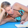 Royalty-Free Stock Photo: Blond woman reading a book whilst sunbathing