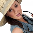 Flirtatious brunette wearing straw hat - Stock Photo