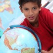 Little boy looking at a globe - Stock Photo