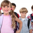Four young children with backpacks - Stock Photo