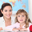 Teacher and girl in school - Stock Photo