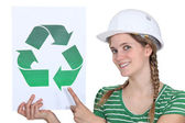 Craftswoman all smiles showing recycling sign — Stock Photo