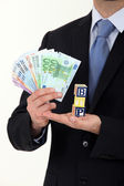 Businessman holding cash and the letters BTP — Stock Photo