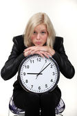Woman leaning on wall clock — Stock Photo