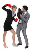 Businesswoman threatening male colleague with boxing gloves — Stock Photo
