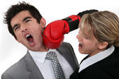 Woman punching her hard-headed colleague — Stock Photo