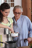 Young woman cooking with her grandmother — Stock Photo