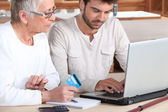 Man helping elderly family member shop on-line — Stock Photo