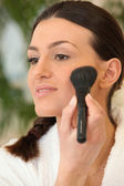 Woman applying blush on the cheek — Stock Photo