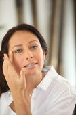 Kvinna tillämpa ögonkräm — Stockfoto