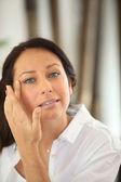 Vrouw toepassing oogcrème — Stockfoto