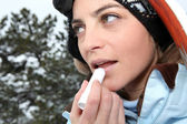 女性スキーヤーのリップ クリームを適用します。 — ストック写真