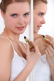 Woman applying lip-stick in mirror — Stock Photo