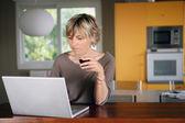 Mujer que trabajaba en su laptop mientras bebe una taza de café — Foto de Stock