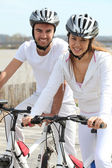 Couple in white on a bicycle — Fotografia Stock