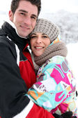 Couple hugging in the snow — Stock Photo