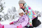 Mother and daughter playing in the snow together — Stock Photo