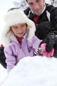 Father and daughter building snow-pile — Stock Photo