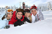 Four young adults laying in the snow — Stock Photo