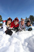 Four friends laying in the snow — Stock Photo