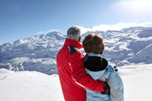 Middle-aged couple stood on secluded snowy mountain — Stock Photo