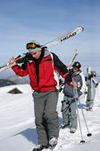 Young men with skis on shoulder — Stock Photo