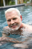 Grey-haired man swimming in the pool — Stock Photo