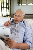 Retiree playing crosswords — Stock Photo
