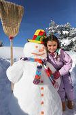 Girl next to snowman — Stock Photo