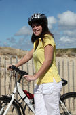 Woman taking a bike ride at the beach — Stock Photo