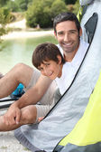 Father and son campink by a lake — Stock Photo
