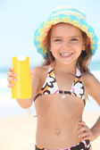 Little girl on the beach with cream — Stock Photo