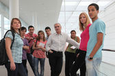 Group of students and teacher stood in corridor — Foto Stock