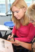 Mulheres em um escritório olhando uma brochura — Foto Stock