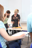 A teacher reviewing a student's work — Stock Photo