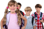 Four young children with backpacks — Stockfoto