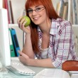 Young student holding apple in library — Stock Photo
