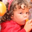 Child inflating balloon - Stockfoto
