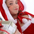 Little girl in a Santa outfit with Christmas presents — Stockfoto