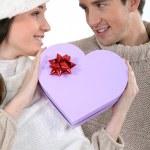 Couple holding heart-shaped box — Stock Photo