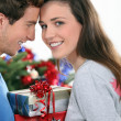 Couple stood by Christmas tree and gifts — Stock Photo #10392497