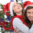 Stock Photo: A couple hugging in front of a Christmas tree