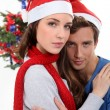 Couple in Santa hats in front of a Christmas tree — Stock Photo