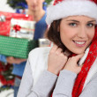 Smiling brunette wearing Christmas cap with boyfriend in background at Christmas — Stock Photo #10392665