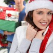 Smiling brunette wearing Christmas cap with boyfriend in background at Christmas — Stock Photo
