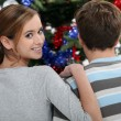 A young couple looking at a Christmas tree. — Stock Photo