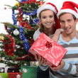 Couple wearing festive hats stood by Christmas tree — Stock Photo