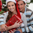 Couple by a Christmas tree — Stock Photo