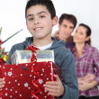 Stock Photo: A boy hugging his Christmas gifts