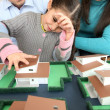Young family looking at model house — Stock Photo